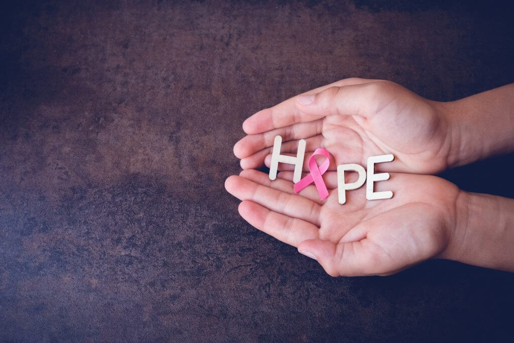 Hands holding HOPE and Pink Ribbon, toning background, Breast cancer awareness and Abdominal cancer awareness