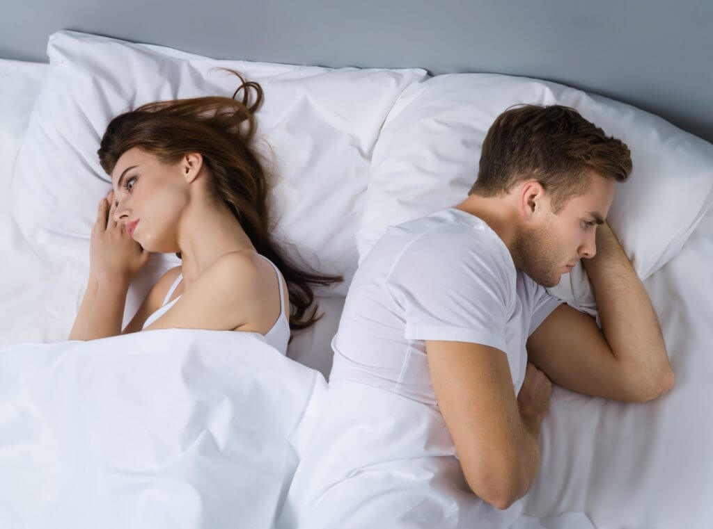 Unhappy young couple on the bed